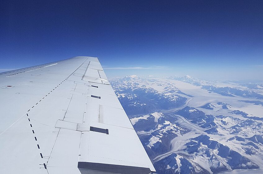 Above the Alaskan mountains and glaciers.